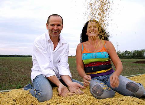 Ein glückliches Paar sitzt auf einem Berg Sojabohnen