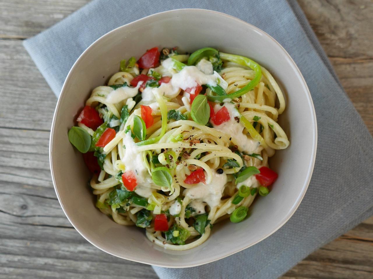 Spagetthi mit Parmesan-Soße in weisser Schüssel